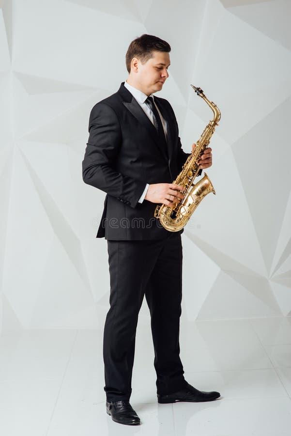 Un hombre juega el cierre del saxofón para arriba imagen de archivo