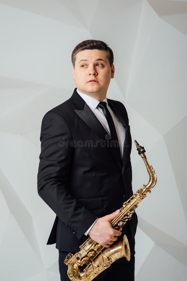 Un hombre juega el cierre del saxofón para arriba foto de archivo