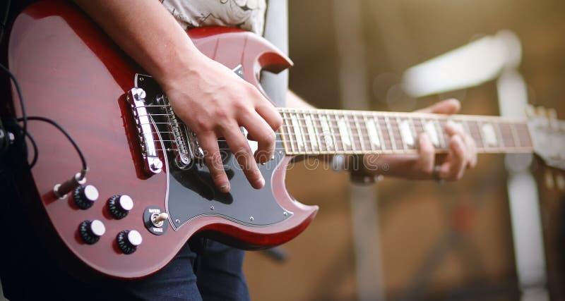 Un hombre juega en una guitarra el?ctrica roja fotos de archivo libres de regalías