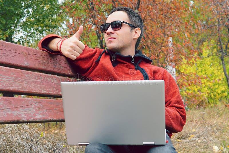 Un hombre lee los mensajes, noticias en el ultrabook y muestra un finger para arriba Eso todo correcto Hombre joven feliz o incon imagen de archivo libre de regalías