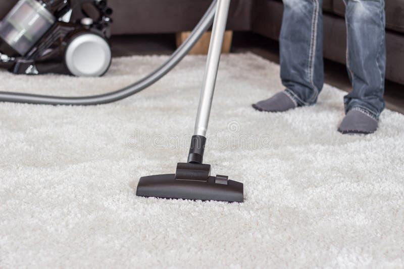 Un hombre limpia la alfombra con un aspirador imágenes de archivo libres de regalías