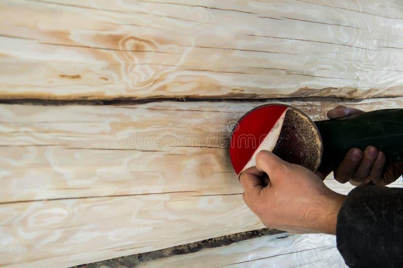Un hombre limpia las pieles de un registro con una m?quina de pulir en una casa de madera fotografía de archivo