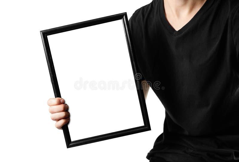 Un hombre lleva a cabo un marco negro A4 Un marco vacío con un fondo blanco Cierre para arriba En el fondo blanco fotografía de archivo