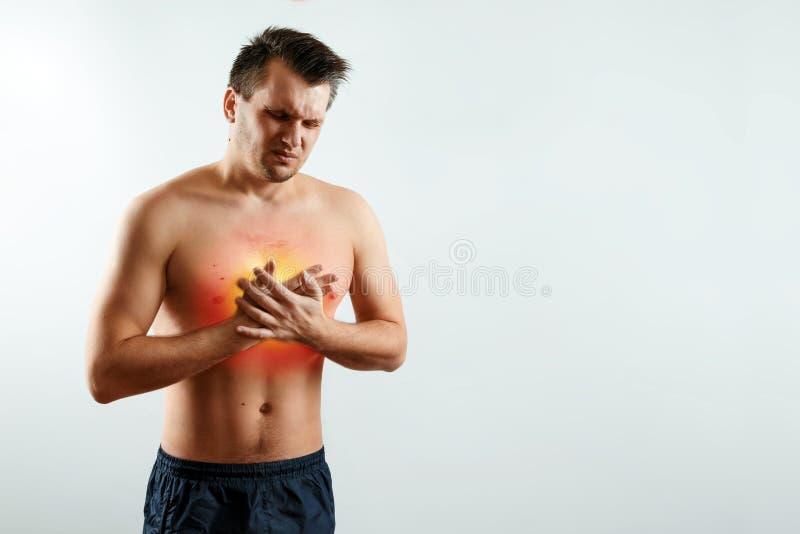 Un hombre lleva a cabo sus manos y región del corazón, dolor de pecho, un dolor en el corazón destacado en rojo, un ataque del co foto de archivo