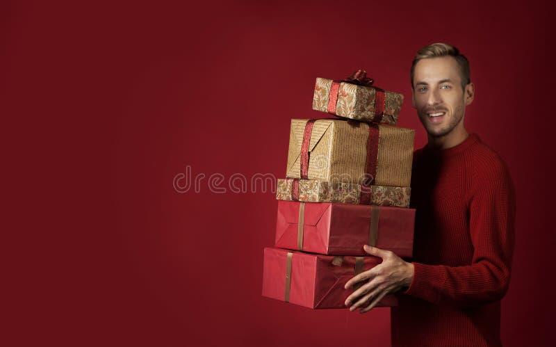 Un hombre lleva los regalos de la Navidad imagenes de archivo
