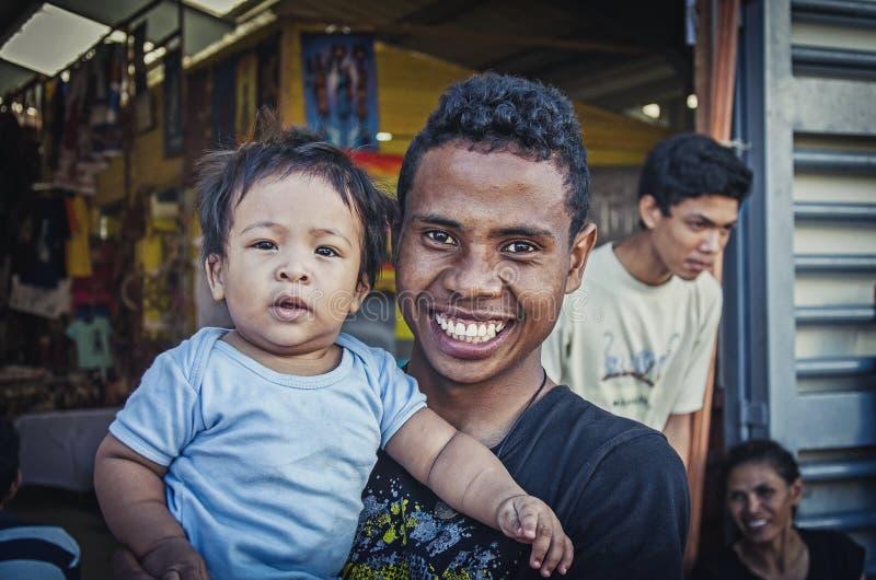 Un hombre local sonriente del aboroginal con el bebé fotografía de archivo libre de regalías
