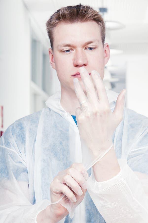 Un hombre más limpio que pone guantes fotos de archivo