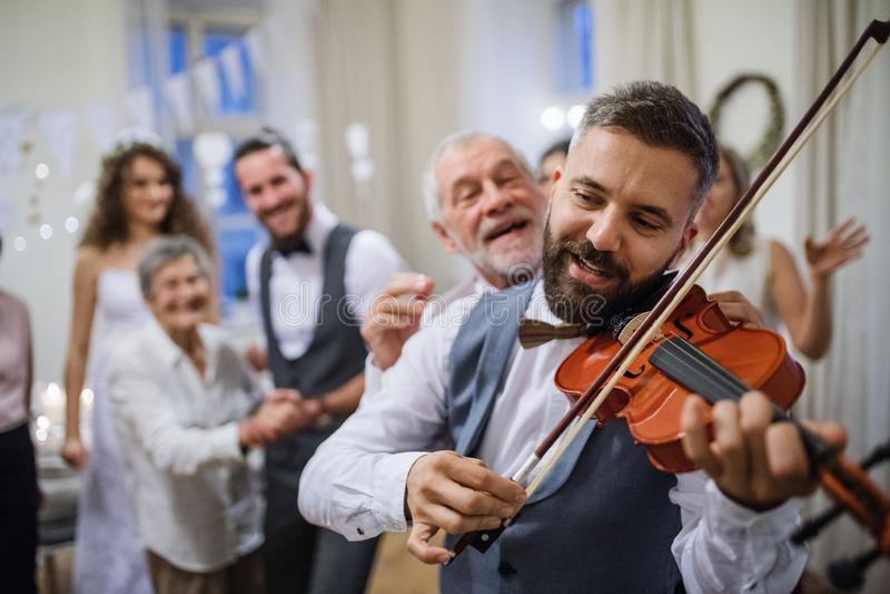 Un hombre maduro que toca un violín en un baile de la recepción nupcial, de novia y del novio imágenes de archivo libres de regalías
