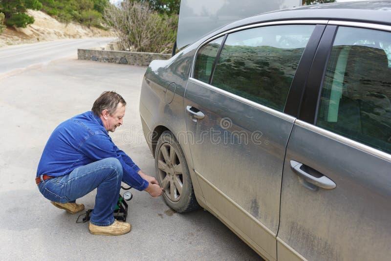 Un hombre mayor bombea la rueda de un coche sucio imágenes de archivo libres de regalías