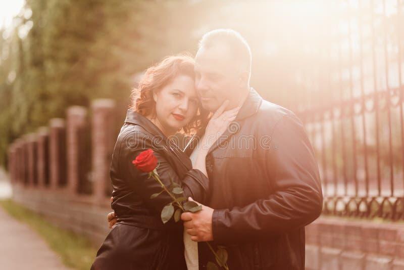 Un hombre mayor da una rosa roja a una mujer Una mujer con los labios rojos abraza a un hombre Pares casados felices Gente en con imágenes de archivo libres de regalías