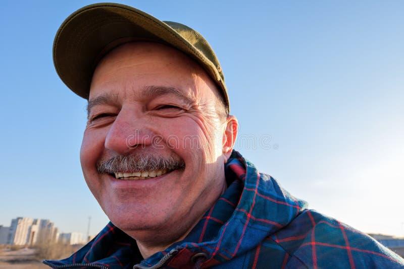 Un hombre mayor en gorra de béisbol mira y sonríe imagen de archivo libre de regalías