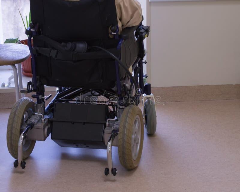 Un hombre mayor en una silla de ruedas que mira hacia fuera la ventana imagenes de archivo