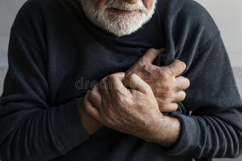 Un hombre mayor está teniendo un ataque del corazón con dolor de pecho imagenes de archivo