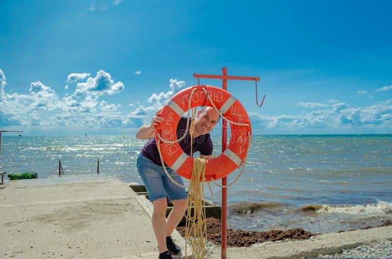 Un hombre mayor mira en la cuerda de salvamento y las sonrisas fotos de archivo libres de regalías