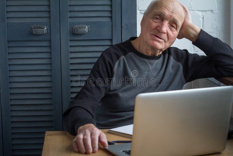 Un hombre mayor mira una pantalla del ordenador portátil, mira una película en casa, foco selectivo fotos de archivo