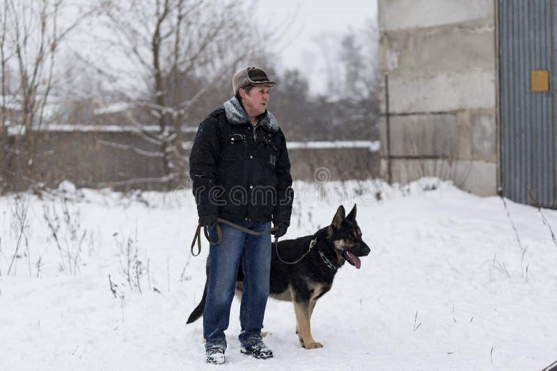 Un hombre mayor que camina con un pastor alemán en el invierno, imagen de archivo