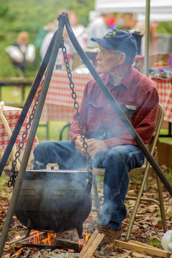 Un hombre mayor que cocina una caldera de la mantequilla de Apple foto de archivo