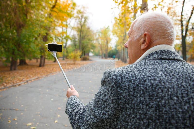 Un hombre mayor que hace selfies en el parque fotografía de archivo