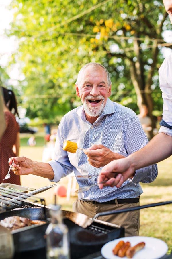 Un hombre mayor que hace una pausa la parrilla, sosteniendo maíz en un partido de la barbacoa imagenes de archivo