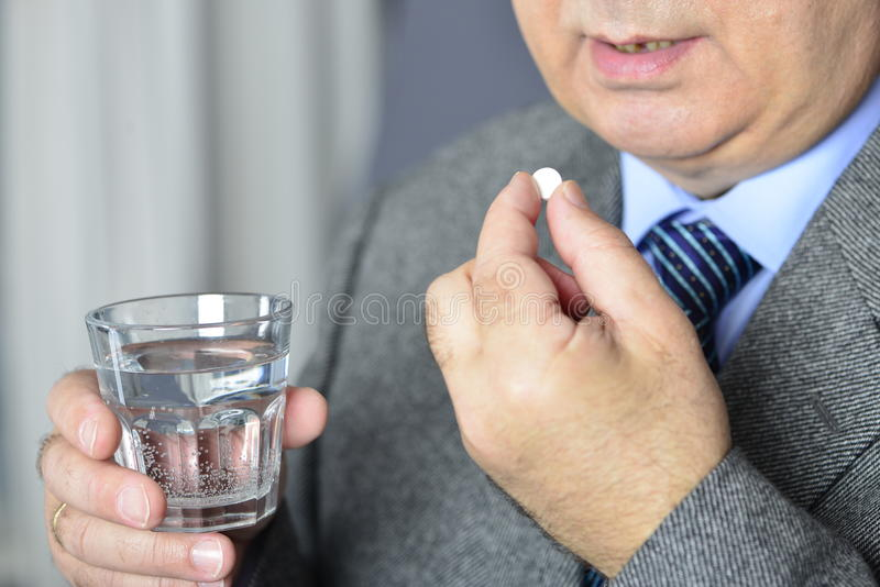 Un hombre mayor que toma la medicina con un vidrio de agua fotos de archivo