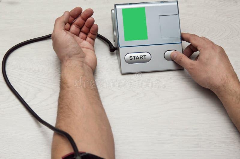 Un hombre mide su presión con un pripore foto de archivo