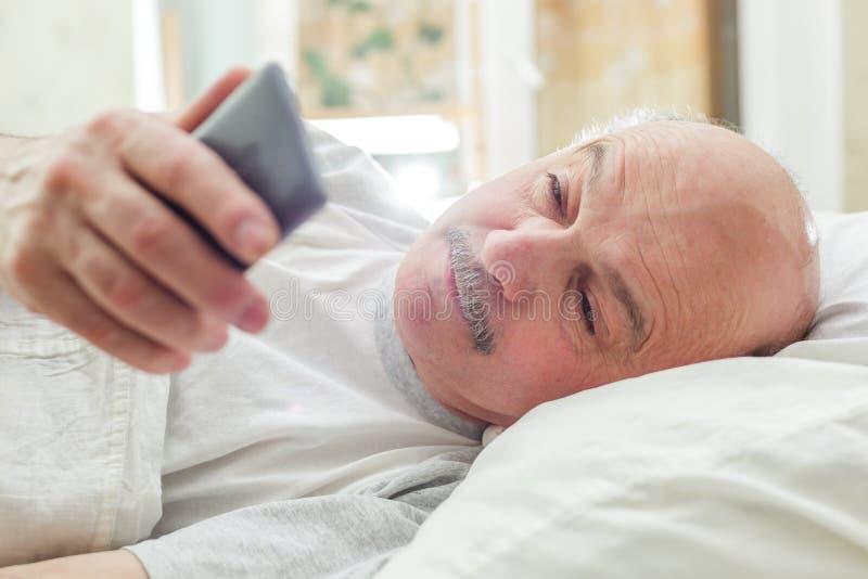 Un hombre mira llamadas faltadas después de despertar fotografía de archivo