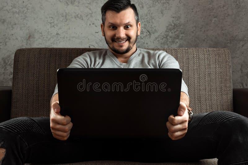 Un hombre mira un v?deo adulto en un ordenador port?til mientras que se sienta en el sof? El concepto de pornograf?a, las necesid imagenes de archivo