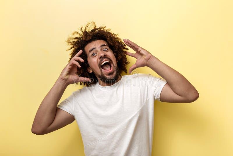 Un hombre moreno de pelo rizado es de grito y que se sostiene los brazos cerca de la cara Emociones brillantes sobre el fondo ama fotos de archivo libres de regalías