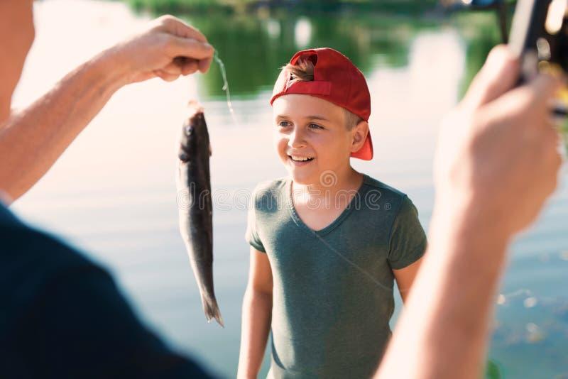 Un hombre muestra a muchacho en un casquillo rojo un pescado que él acaba de coger en su giro fotografía de archivo