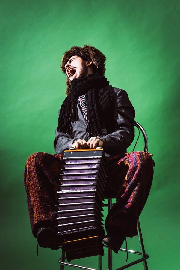 Un hombre muy positivo con un acordeón que presenta en el estudio foto de archivo