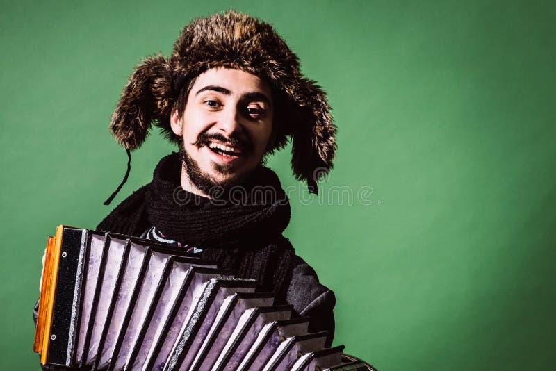 Un hombre muy positivo con un acordeón que presenta en el estudio imágenes de archivo libres de regalías