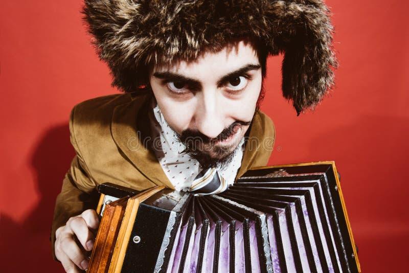 Un hombre muy positivo con un acordeón que presenta en el estudio fotografía de archivo libre de regalías