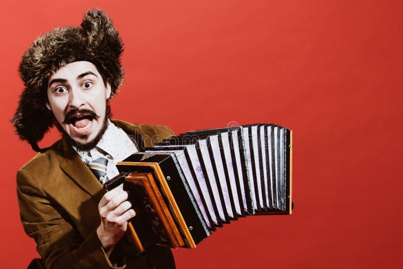 Un hombre muy positivo con un acordeón que presenta en el estudio imagenes de archivo