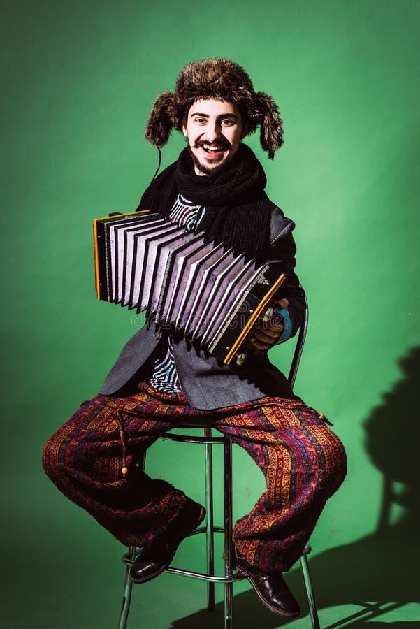 Un hombre muy positivo con un acordeón que presenta en el estudio fotografía de archivo