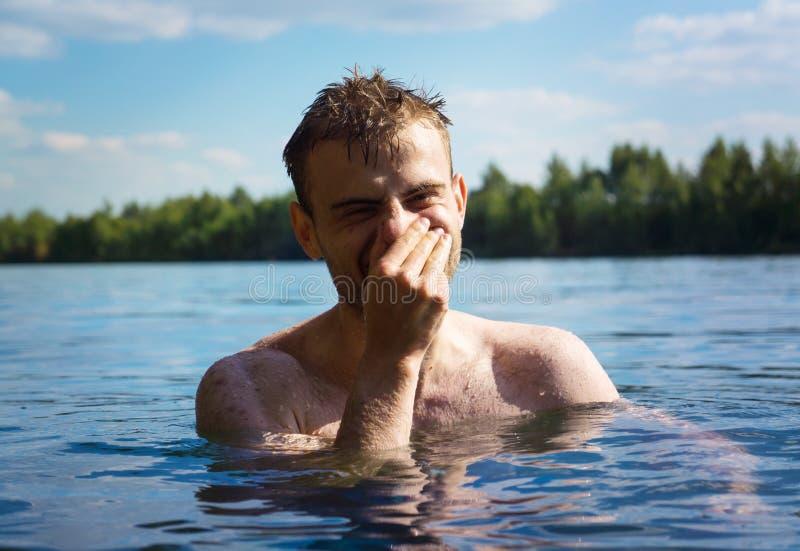 Un hombre nada en el agua de un lago, goza el descansar en el agua, divirtiéndose fotos de archivo libres de regalías