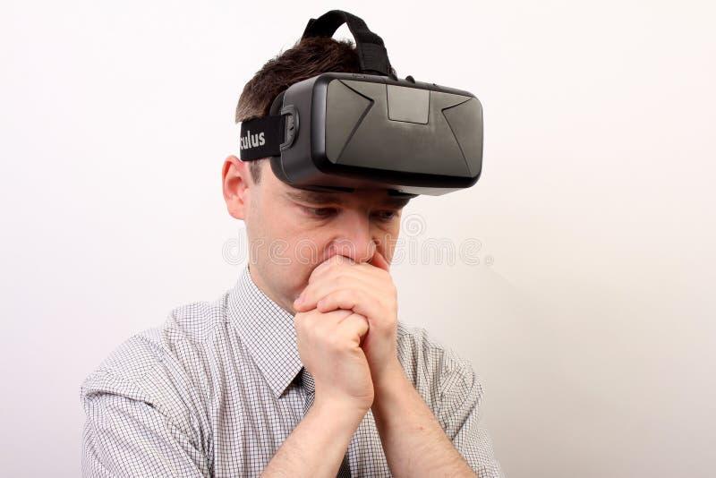 Un hombre nauseabundo, mareado, molestado que lleva las auriculares de la realidad virtual de la grieta VR de Oculus después de u foto de archivo
