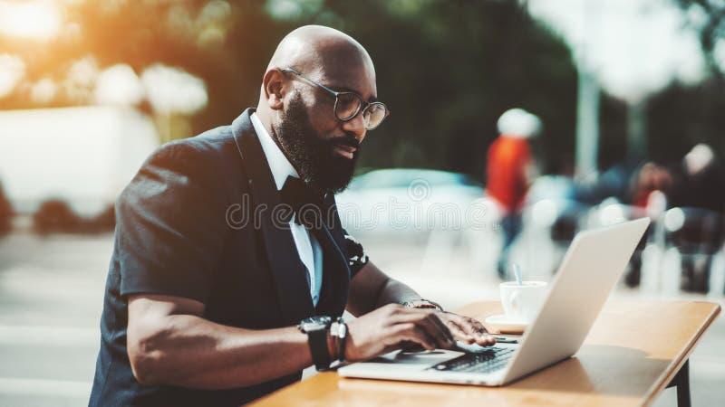 Un hombre negro con un ordenador port?til en un caf? imagen de archivo