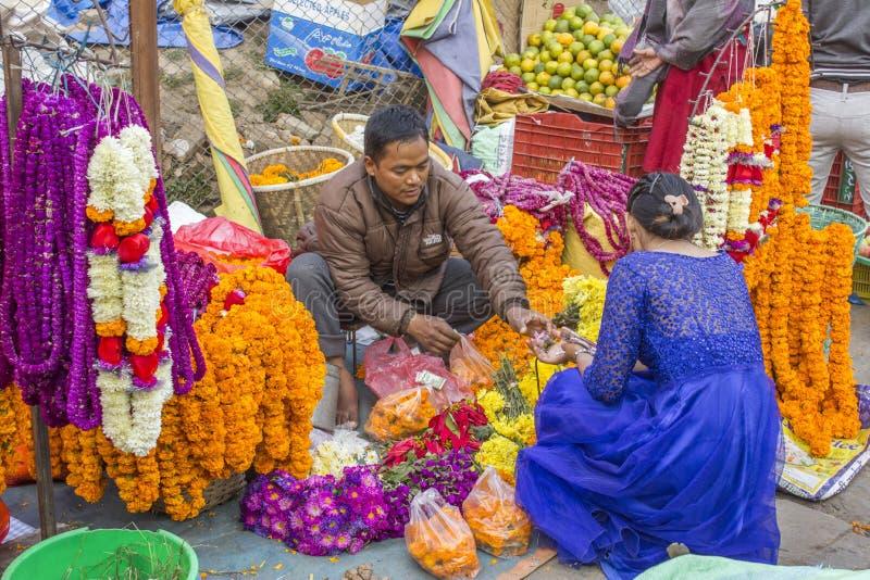 Un hombre Nepali vende las flores a una mujer en un vestido azul, vendedores ambulantes de fresco colorido brillante imagen de archivo libre de regalías