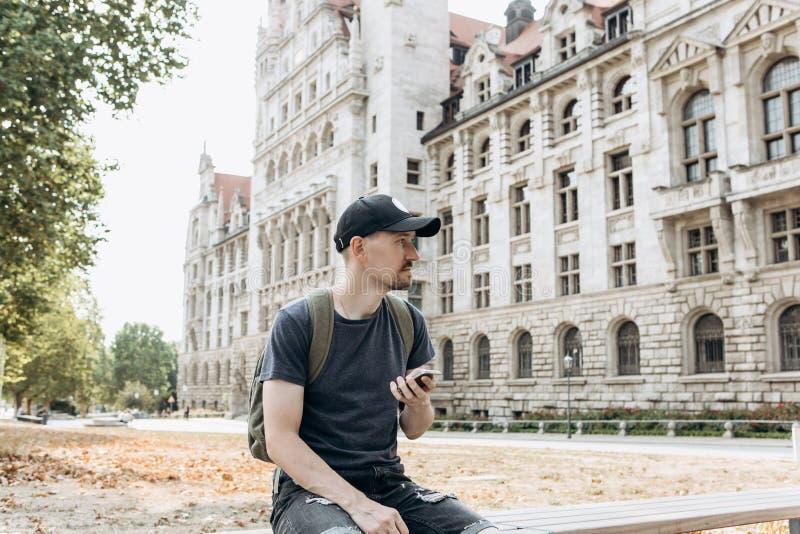 Un hombre o un muchacho turístico con una mochila utiliza un teléfono móvil fotos de archivo