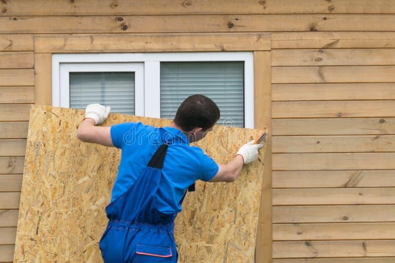 Un hombre obstruye una ventana con un pedazo grande de madera contrachapada antes de un desastre natural, un huracán fotos de archivo libres de regalías