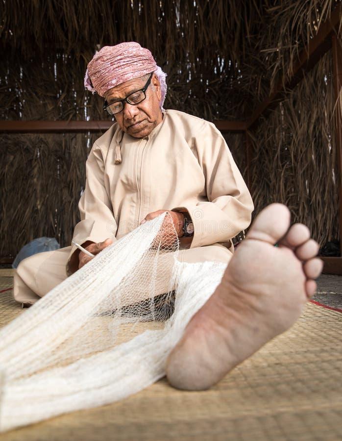Un hombre omaní que teje una red de pesca foto de archivo