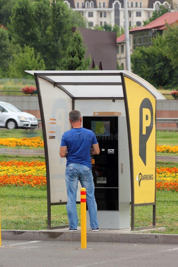 Un hombre paga los servicios del estacionamiento pagado en el termi del pago imagen de archivo libre de regalías