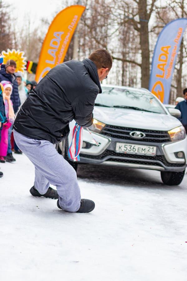 Un hombre participa en la competencia para el día de fiesta Maslenitsa y arrastra un coche ligero de LADA en una cuerda Ciudad de fotografía de archivo
