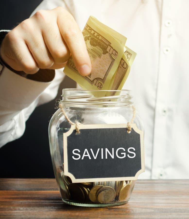 Un hombre pone dólares en un tarro de cristal con los ahorros de la palabra El concepto de manejar un presupuesto familiar Distri imagen de archivo