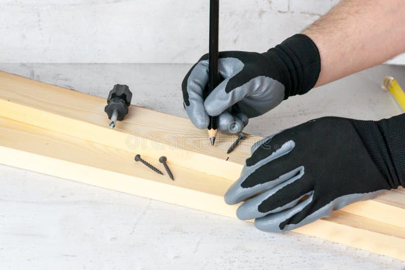 Un hombre pone marcas en las barras de madera con un lápiz para el trabajo adicional con una sierra Concepto de Diy en casa foto de archivo libre de regalías