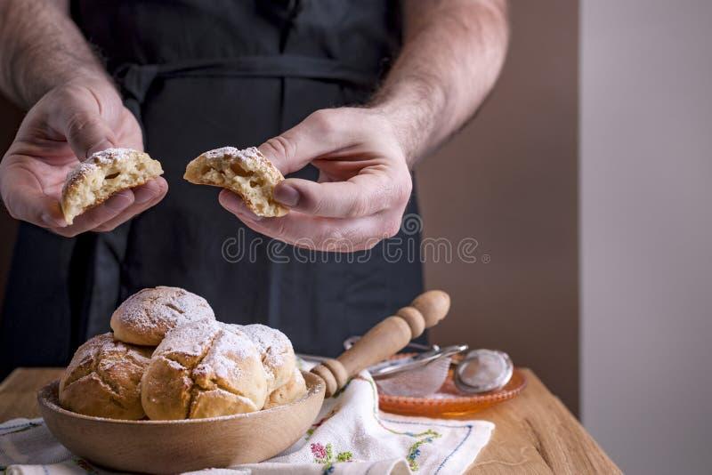 Un hombre prepara los anillos de espuma con el azúcar en polvo Pasteles hechos en casa del invierno para el día de fiesta Espacio fotos de archivo