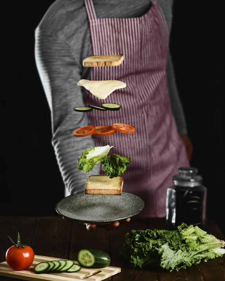 Un hombre prepara los ingredientes para un bocadillo vegetariano delicioso foto de archivo