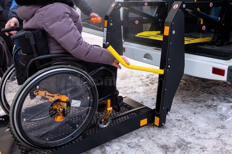 Un hombre presiona un botón en el panel de control para coger a una mujer en una silla de ruedas en un taxi para los minusválidos fotos de archivo