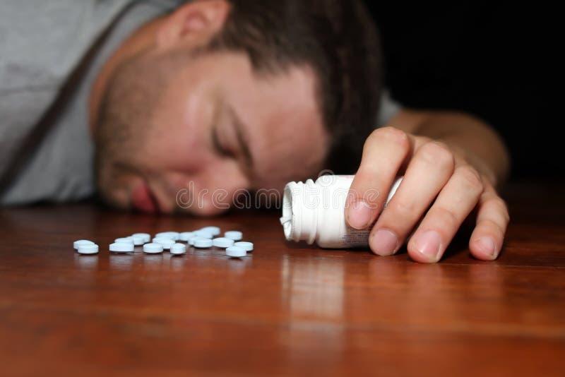Un hombre que aparece overdosed en píldoras imagen de archivo libre de regalías