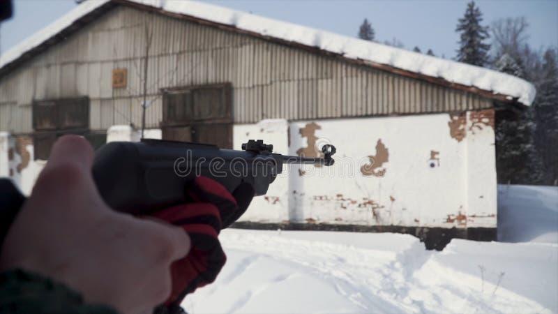 Un hombre que apunta un arma de la pelotilla hacia una blanco, practicando el suyo objetivo en el invierno clip La pistola en cam imagen de archivo